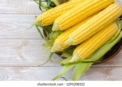 Ripe corn in a clay bowl on a light wooden background.