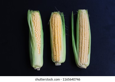 Ripe corn and grain on a black background, top view, space for copy