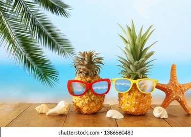 Ripe couple pineapple in stylish sunglasses over wooden table or deck against blue sea, relaxing. Tropical summer vacation concept.