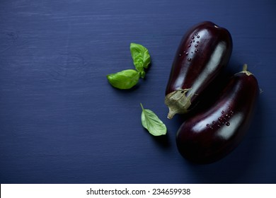 Ripe eggplants over dark blue wooden background, copyspace
