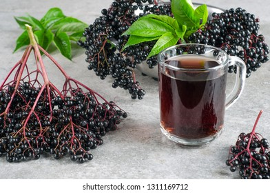 Ripe elderberry with green leaves and drink in a glass on a gray textured background.