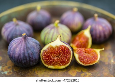 Ripe figs in the old bowl on a stone background.