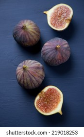 Ripe figs over dark blue wooden background, above view
