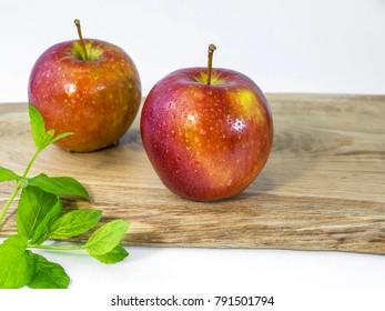 Ripe fresh apple fruit on a wooden oak plate with mint leaves