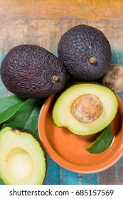 Ripe fresh avocado with leaves on blue wooden table - healthy food concept