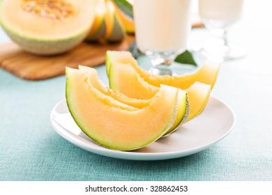Ripe fresh cantaloupe slices on white plate