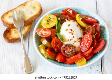 Ripe fresh colorful tomatoes salad with mozzarella cheese.
