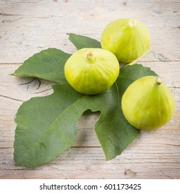 Ripe fresh figs with leaf on wooden background