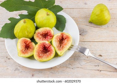 Ripe fresh green figs on wooden background