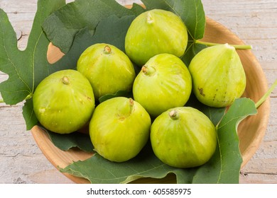 Ripe fresh green figs on wooden plate