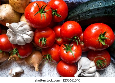 Ripe fresh harvested vegetables on table. Onions, tomatoes, garlic, pepper, zucchini in kitchen. Making delicious vegetarian meal or canning veggies for winter in jars. Concept of healthy eating