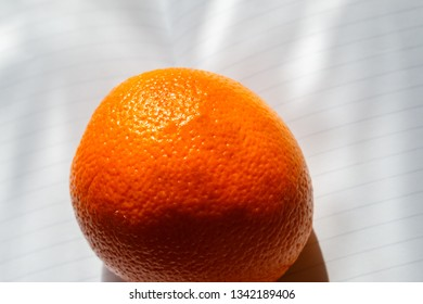 ripe and fresh orange in the sun rays on the white paper background