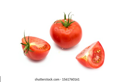 ripe fresh organic tomato, half and a quarter of tomato in drops of dew isolated on a white background