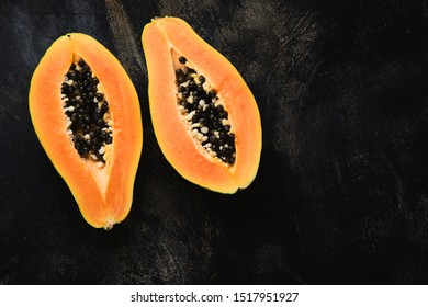 Ripe fresh papaya fruit on black background, raw vegan diet concept. Top view with copy space
