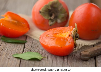 Ripe fresh persimmon on a brown wooden background. Slices