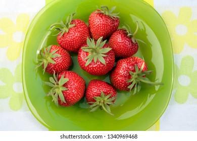 Ripe fresh strawberries on the green plate