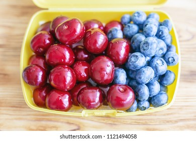 Ripe fresh tasty bio cherries and bluberries in plastic lunchbox . Organic sweet berries takeaway quick food for picnic. Healthy snacks. Wooden table on background