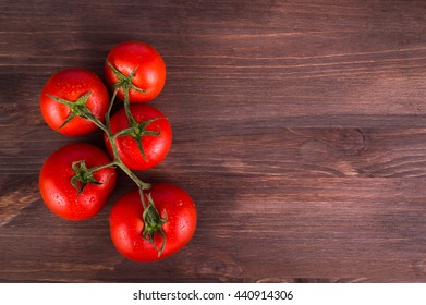 Ripe fresh tomatoes on a branch on a wooden table. Space for text.
