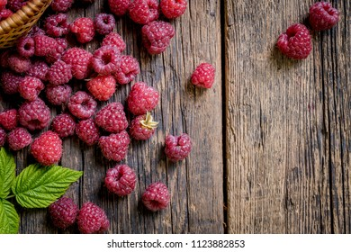 Ripe, freshly picked raspberries, on rustic wooden old table surface. Flat lay.