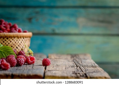 Ripe, freshly picked raspberries, on rustic wooden old table surface.
