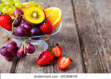 Ripe fruits on a transparent plate on a wooden background. Healthy eating.