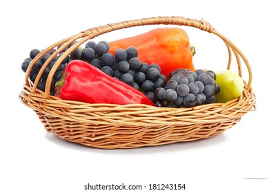 The ripe fruits of pepper red, yellow and grapes in a wicker basket. Presented on a white background.