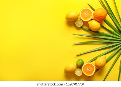 Ripe fruits and tropical leaf on color background