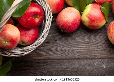 Ripe garden apple fruits in basket on wooden table. Top view flat lay with copy space