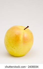 Ripe golden delicious apple with sun-kissed highlights