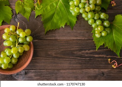 Ripe grape cluster of white grapes in a bowl on a wooden table with green leaves of grapes. Vintage grape berries.