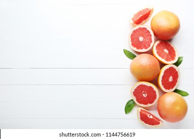 Ripe grapefruits with green leafs on white wooden table