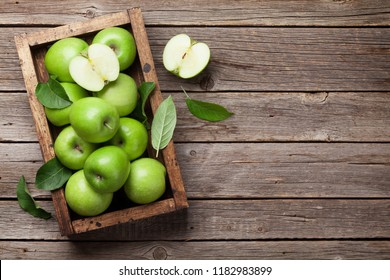 Ripe green apples box on wooden table. Top view with space for your text
