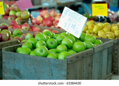 Ripe green apples in box with a price tag
