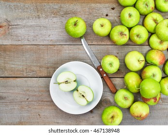 Ripe green apples in a plate with a sharp knife on a wooden background. Free space for text. Top view