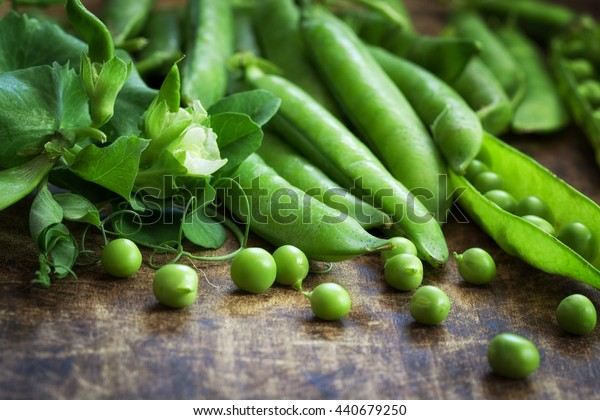 Ripe Green peas on wooden table