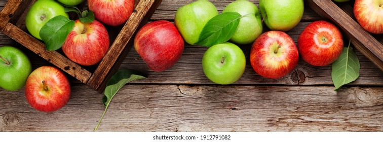 Ripe green and red apples in wooden boxes. Top view flat lay