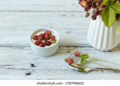 Ripe and green strawberries with leaves and flowers in a ceramic vase on a white background. Dessert with cream and berries in a white bowl. Light snack
