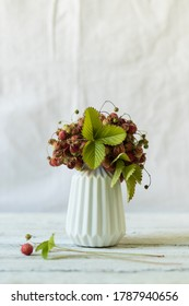 Ripe and green strawberries with leaves and flowers in a ceramic vase on a white background