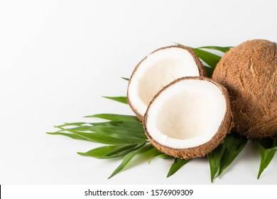 Noix de coco mûr à moitié découpée sur fond bois. Crème de coco et huile.