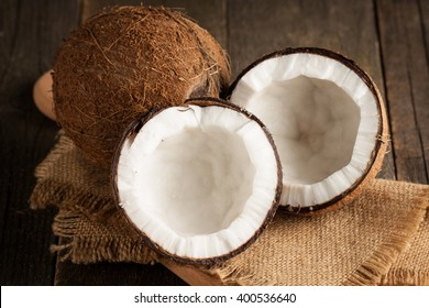 Ripe half cut coconut on a wooden background. Ripe half cut coconut with milk on a wooden background