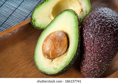 Ripe halved avocado on plate. Indoors closeup.