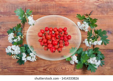 Ripe hawthorn fruits on the transparent glass saucer among flowering twigs of hawthorn plant on an old wooden surface