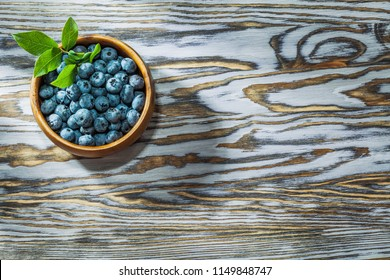 Ripe huckleberries in round wooden bowl.