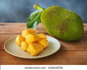 Ripe jackfruit flesh in white plate on wooden table for tropical fruit or meat substitute concept.