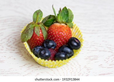 Ripe and juicy berries and fruits lie in a yellow paper plate. Close-up. macro