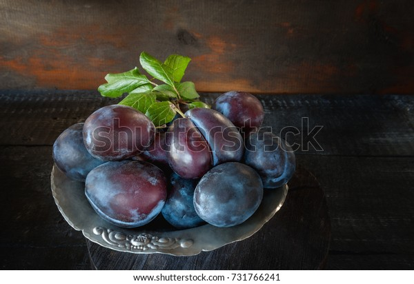 Ripe and juicy blue plums in a wicker basket in a rustic style. Happy Thanksgiving. Copy space.