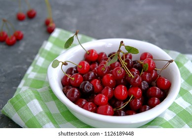Ripe juicy cherries in a white bowl on a dark gray background. Healhty eating concept.