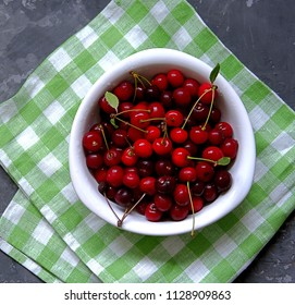 Ripe juicy cherries in a white bowl on a dark gray background. Healhty eating and summer concept.