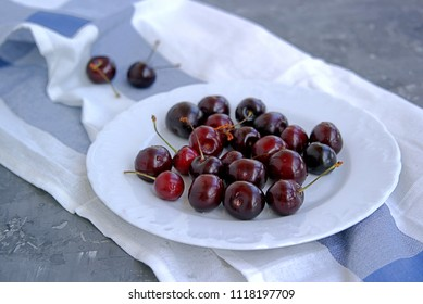 Ripe juicy cherry on a white plate. Healhty dessert and summer concept.