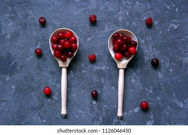 Ripe juicy cherry in wooden spoons on a dark gray concrete background. Summer concept
